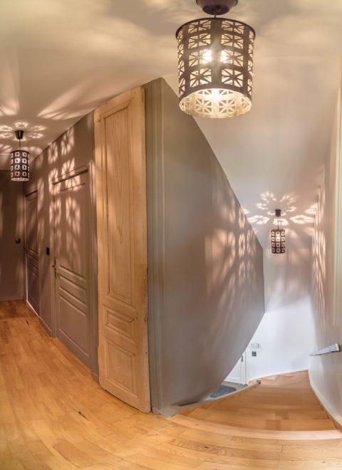 Le couloir a été repeint en foncé ce qui fait ressortir la jolie porte ancienne en bois brute.