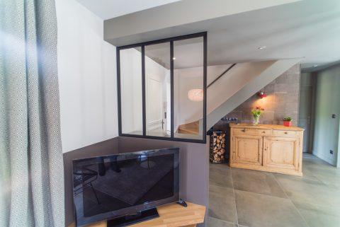 L'entrée délimitée par une verrière . Le coin tv est réchauffé par une couleur foncé.