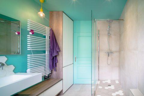 La porte d'entrée décalée permet d'accueillir la douche mais aussi un rangement tout en hauteur.
