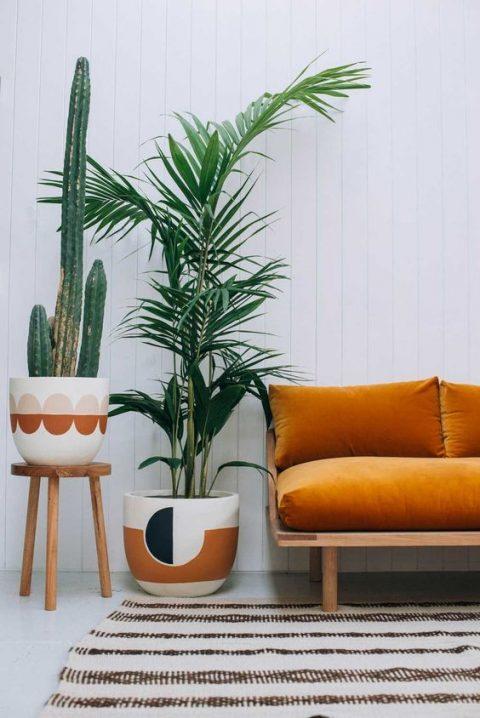 Canapé avec une assise généreuse de couleur orange accompagné de pot pour plantes à la décoration harmonieuse.