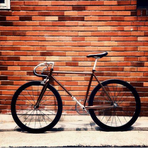 Vélo noir de course très design posé contre un mur de brique.